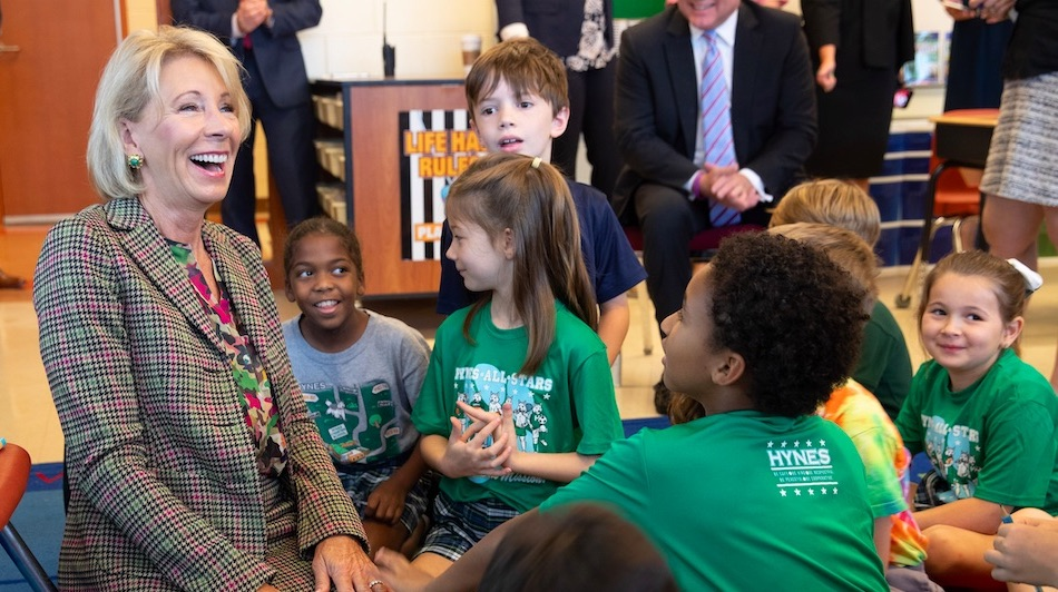 Secretary Betsy DeVos sitting with elementary age children in a classroom.
